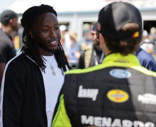 <em>Alvin Kamara chats with Ryan Blaney before the Ally 400 (Donald Page/Getty Images).</em>