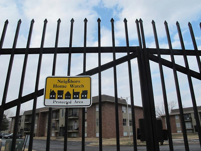 A black wrought-iron gate surrounds the Fairmont Terrace apartment complex on Thursday, Feb. 7, 2013, in Tulsa, Okla. The fence was supposed to act as a deterrent to criminal activity, but   four women were shot dead at the complex last month. (AP Photo/Justin Juozapavicius)
