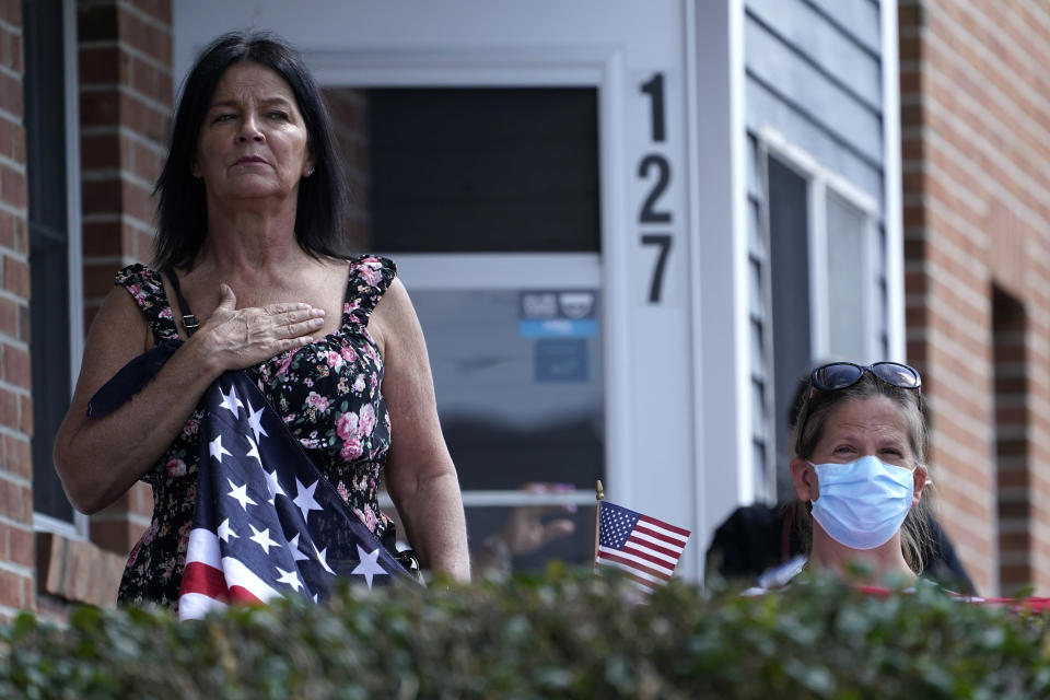 Residents watch the funeral procession for Sgt. Johanny Rosario Pichardo, a U.S. Marine who was among 13 service members killed in a suicide bombing in Afghanistan, in Lawrence, Mass, Saturday, Sept. 11, 2021. (AP Photo/Robert F. Bukaty)