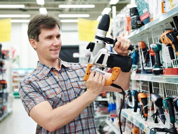 A customer holding up a power drill at the hardware store.