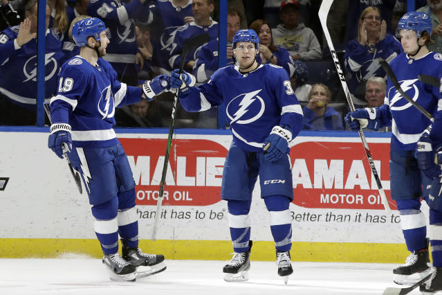 Tampa Bay Lightning center Yanni Gourde, center, celebrates with center Barclay Goodrow, left, and defenseman Mikhail Sergachev, right, after scoring against the Toronto Maple Leafs during the third period of an NHL hockey game Tuesday, Feb. 25, 2020, in Tampa, Fla. (AP Photo/Chris O'Meara)