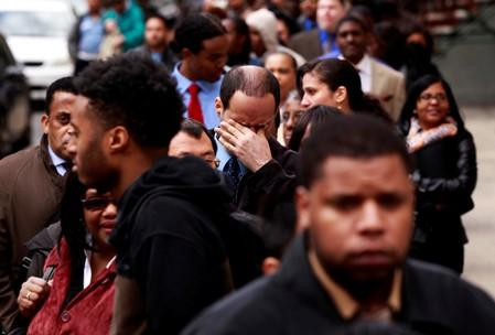 FILE PHOTO: FILE PHOTO: Man rubs his eyes as he waits in a line of jobseekers, to attend the Dr. Martin Luther King Jr. career fair held by the New York State department of Labor in New York