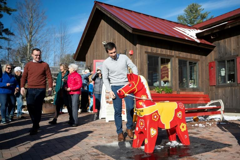 Democratic presidential hopeful Mayor Pete Buttigieg (C) looks at a toy horse as he and his husband Chasten (L) depart Polly's Pancake Parlor in Franconia, NH, on November 10, 2019, as they continue the 4-day bus tour (AFP Photo/JIM WATSON)