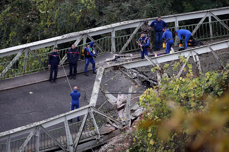 Picture of rescue workers on the collapsed bridge, where two people died on Monday in Southern France.