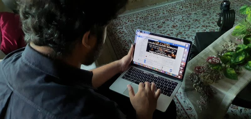Zoraiz Riaz, who admins a Facebook group called Corona Recovered Warriors! to coordinate convalescent plasma donations, works on a computer at his residence in Lahore,