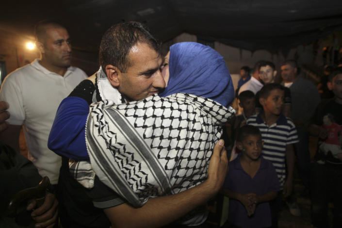 Released Palestinian prisoner Hosni Sawalha is hugged upon his arrival to his family house in Azmout village near Nablus in the West Bank, Wednesday, Aug. 14, 2013. Israel agreed to release 26 Palestinian prisoners, most of them held for deadly attacks and most have already served around 20 years, as a part of a U.S.-brokered deal that led to a resumption of Mideast negotiations. (AP Photo / Nasser Ishtayeh)