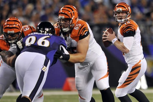 Cincinnati Bengals quarterback Andy Dalton 914) looks for a receiver as center Jeff Faine (62) and guard Clint Boling (65) hold back Baltimore Ravens nose tackle Maake Kemoeatu in the first half of an NFL football game in Baltimore, Monday, Sept. 10, 2012. (AP Photo/Gail Burton)
