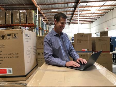 Luke Peters, President and CEO of NewAir, works on his laptop computer at NewAir's warehouse in Cypress
