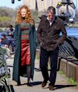 <p>This long teal trench is another design by - yep, you guessed it! - Max Mara. In this scene with Jonathan, Grace wears it layered over a sparkly striped turtleneck by A.L.C. and a red faux-leather pencil skirt.</p>