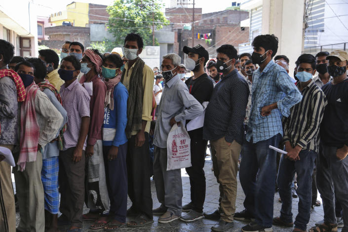 FILE- In this April 19, 2021 file photo, people wearing face masks as a precaution against the coronavirus line up without any physical distancing to get tested for COVID-19 at a government hospital in Jammu, India. India's health system is collapsing under the worst surge in coronavirus infections that it has seen so far. Medical oxygen is scarce. Intensive care units are full. Nearly all ventilators are in use, and the dead are piling up at crematoriums and graveyards. Such tragedies are familiar from surges in other parts of the world — but were largely unknown in India. (AP Photo/Channi Anand, File)