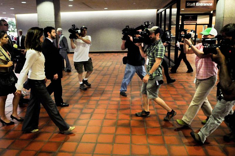 Amy Senser, left, is surrounded by the media as she enters the Hennepin County Government Center before hearing the jury's verdict in her hit-and-run case on Thursday, May 3, 2012, in Minneapolis. Amy Senser was convicted of leaving the scene of an accident and failure to promptly report an accident, both criminal vehicular homicide charges, in the August death of Anousone Phanthavong. She was acquitted of a third felony charge of gross negligence. She was also convicted of misdemeanor careless driving. (AP Photo/Pioneer Press, Jean Pieri)