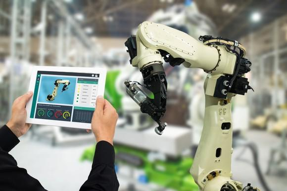 a man holding up a tablet to monitor a manufacturing robotic arm