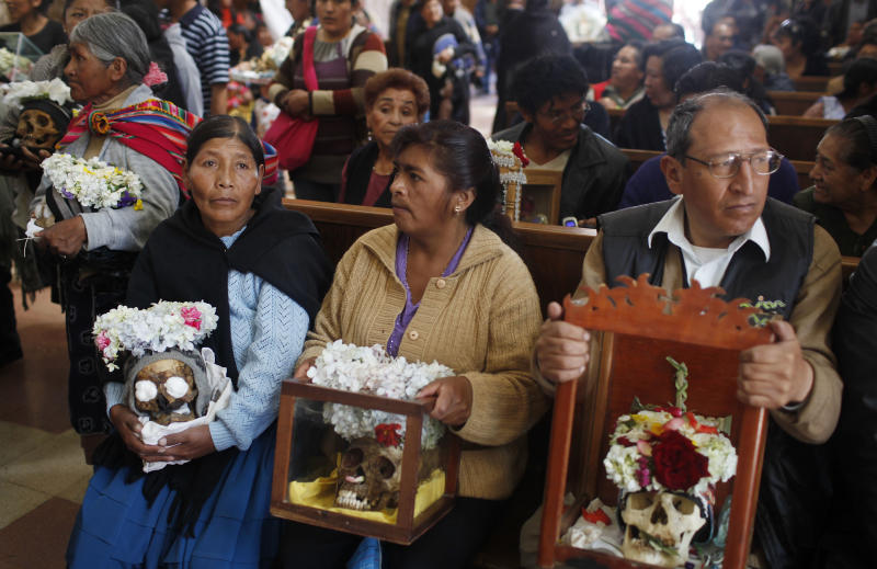 "People holds decorated human skulls or ""natitas"" as they wait to be greeted by the priest inside the Cementerio General chapel during the Natitas Festival celebrations in La Paz, Bolivia, Friday, Nov. 8, 2013. The Roman Catholic church considers the skull festival to be pagan, but it doesn't prohibit people from participating in it. Mass was not being held at the chapel on Friday, but a bowl of holy water was left out so people could bless the skulls they were carrying in the ritual celebrated a week after Day of the Dead. (AP Photo/Juan Karita)"