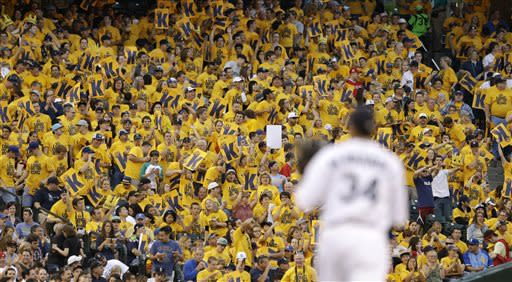 """Fans wearing yellow """"King's Court"""" tee shirts stand and cheer after Seattle Mariners starting pitcher Felix Hernandez threw a strikeout against the Los Angeles Angels in the sixth inning of a baseball game Saturday, July 13, 2013, in Seattle. (AP Photo/Elaine Thompson)"""