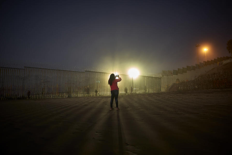 FILE- A woman records with her phone, as floodlights from the United States light up the newly-fortified border wall Thursday, Jan. 10, 2019, along the beach in Tijuana, Mexico. Top Trump administration officials will visit South Texas five days before Election Day to announce they have completed 400 miles of U.S.-Mexico border wall, attempting to show progress on perhaps the president's best-known campaign promise four years ago. But most of the wall went up in areas that already had smaller barriers. (AP Photo/Gregory Bull)