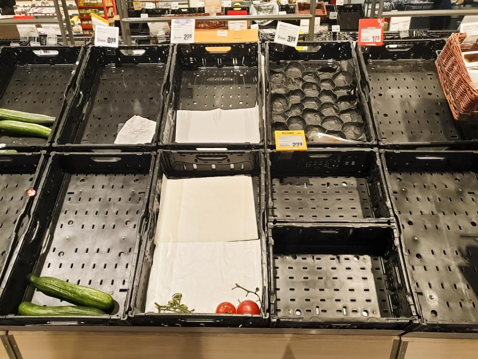 Nearly empty vegetable crates in a grocery store