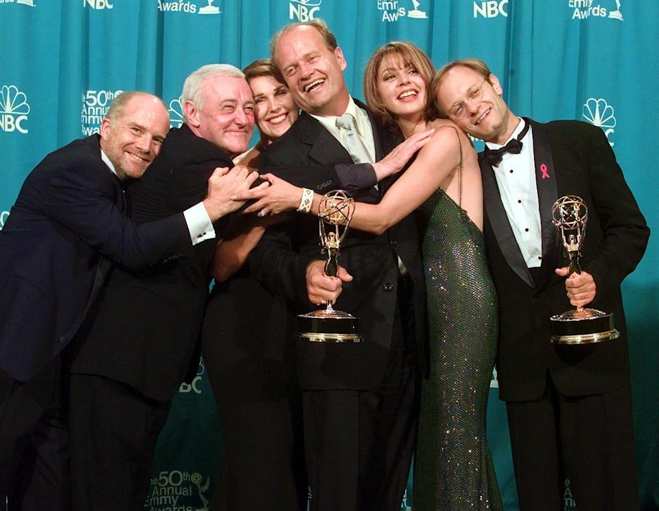 """FILE – In this Sept. 13, 1998 file photo, cast members of """"Frasier,"""" from left, Dan Butler, John Mahoney, Peri Gilpin, Kelsey Grammer, Jane Leeves and David Hyde Pierce, winners of the Emmy for Outstanding Comedy Series, pose backstage at the 50th Annual Primetime Emmy Awards in Los Angeles. (AP Photo/Reed Saxon, File)"""