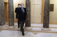 Followed by a staffer, Senate Majority Leader Mitch McConnell of Ky., right, leaves the Capitol for the day, Tuesday, Dec. 29, 2020, on Capitol Hill in Washington. (AP Photo/Jacquelyn Martin)