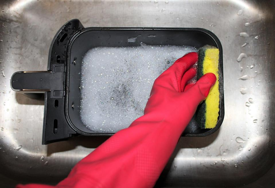 <p>Once you've removed the crisper plate, wash the inside and outside of the basket by hand with warm, soapy water. Again, all air fryers are different, so check the cleaning instructions on yours to make sure the basket is submergible. Some air fryer baskets are dishwasher-safe, but I prefer to wash mine by hand.</p>