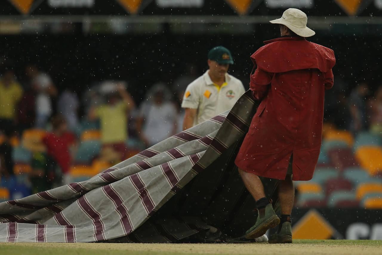 BRISBANE, AUSTRALIA - NOVEMBER 24:  Ground staff cover the pitch as rain delays play during day four of the First Ashes Test match between Australia and England at The Gabba on November 24, 2013 in Brisbane, Australia.  (Photo by Mark Kolbe/Getty Images)