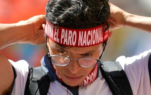 """A student puts on a headband reading """"National Strike"""" as he takes part in an anti-government protest in Bogota"""