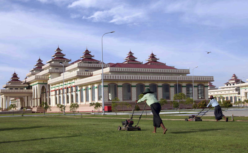 In this Tuesday, Nov. 26, 2013 photo, workers tend the lawns of Myanmar's massive parliamentary complex, which includes 31 buildings to symbolize Buddhism's 31 planes of existence, in Naypyitaw. The buildings are one of many grandiose edifices built by the former military regime as it moved the capital from Yangon to a remote area of scrubland eight years ago. Naypyitaw has grown substantially since then but some still doubt it will become a truly viable city. (AP Photo/Khin Maung Win)