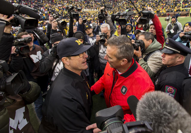 Michigan head coach Jim Harbaugh and Ohio State head coach Urban Meyer share a moment after last year's game. (AP)