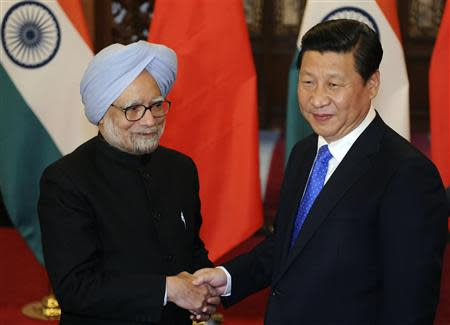 China's President Xi shakes hands with India's PM Singh before their meeting in Beijing