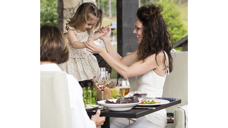 Family lunch outdoors at the Tavern, one of five restaurants at the resort. - Credit: Ball & Albanese
