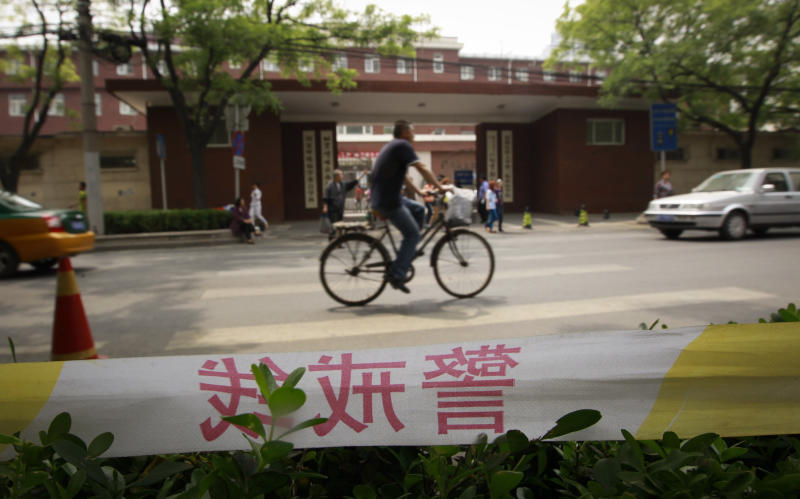 A man pedals his bicycle in front of a hospital where Chinese legal activist Chen Guangcheng is receiving medical treatment in Beijing, Wednesday, May 9, 2012. Chen who triggered a diplomatic dispute between China and the United States said Monday he is confident that Beijing will hold up its end of a tentative deal to let him study overseas. (AP Photo/Vincent Thian)