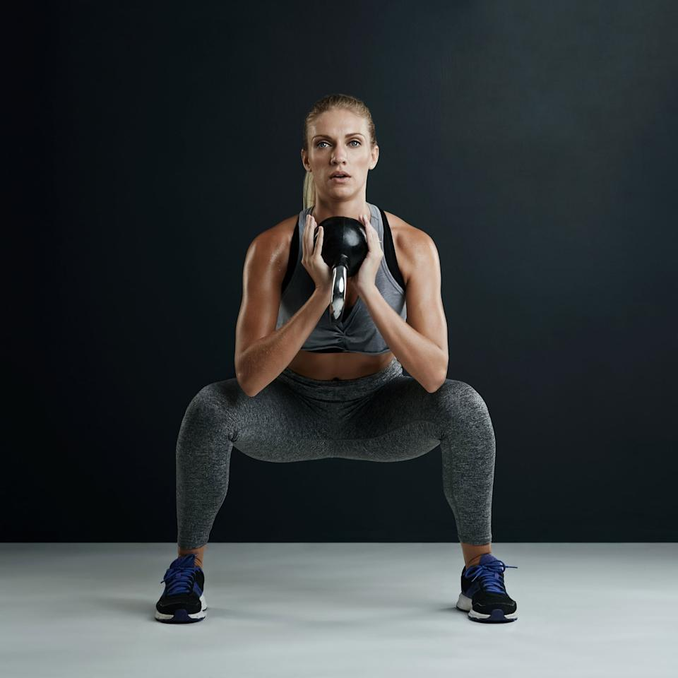 """<p>""""This is the best squat to feel your glutes the most,"""" Tara told POPSUGAR. """"Because the weight is in front, you are hinging and leaning slightly forward,"""" then pushing through your heels and squeezing your glutes when you stand.</p> <ul> <li>Stand with your feet slightly wider than hip-distance apart, with your toes pointed slightly outward. </li> <li>Hold a heavy kettlebell (20 to 40 pounds) in front of you with palms facing each other. Either hold it upside down at the base (as pictured) or right side up by the lower portion of the handle (aka the horns). Pull your elbows in toward your sides.</li> <li>Keep your chest lifted, and squat down until your thighs are parallel to the ground. The kettlebell and your arms should stay inside of your legs and close to your body at all times. </li> <li>Pause, then slowly stand back up.</li> <li>This counts as one rep.</li> </ul>"""