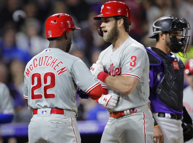 Philadelphia Phillies' Bryce Harper (3) celebrates his three-run home run that also scored teammate Andrew McCutchen (22) and Cesar Hernandez in the seventh inning of a baseball game against the Colorado Rockies in Denver, Saturday, April 20, 2019. (AP Photo/Joe Mahoney)