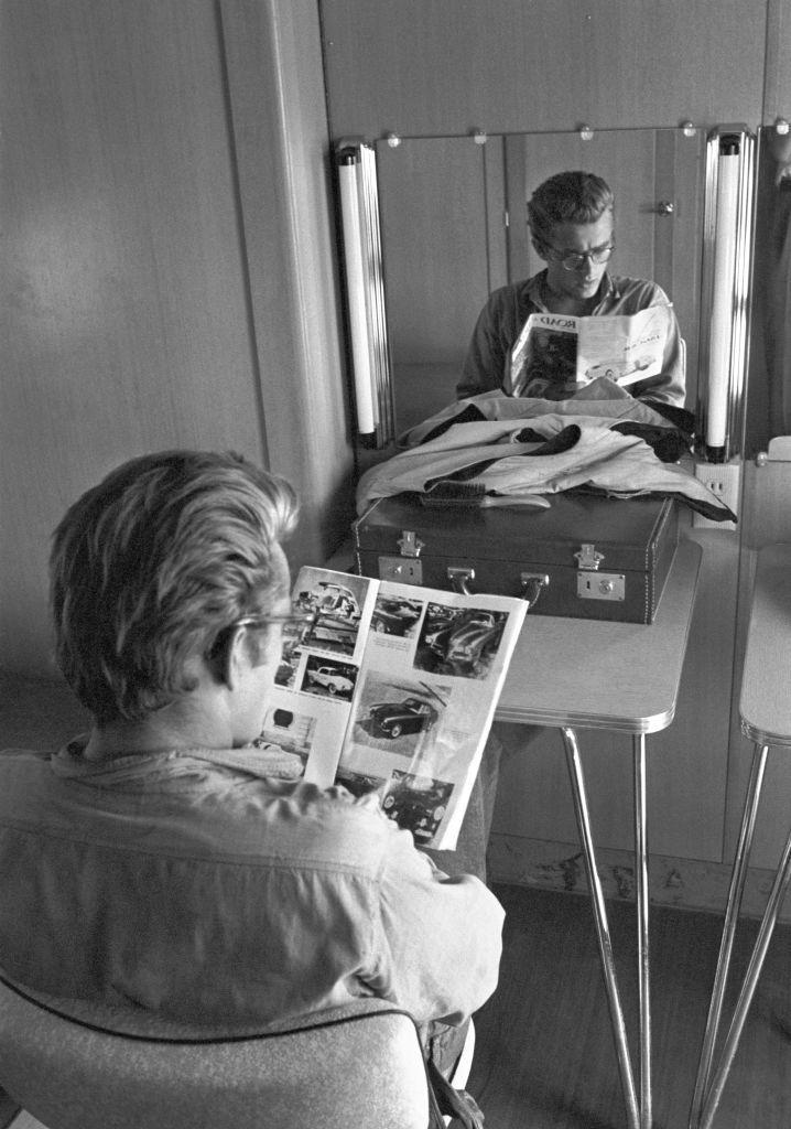 <p>Here, Dean is seen flipping through a racing magazine while in his dressing room on set. While working on <em>Giant</em>, the actor was banned from racing, as it was considered too dangerous. </p>