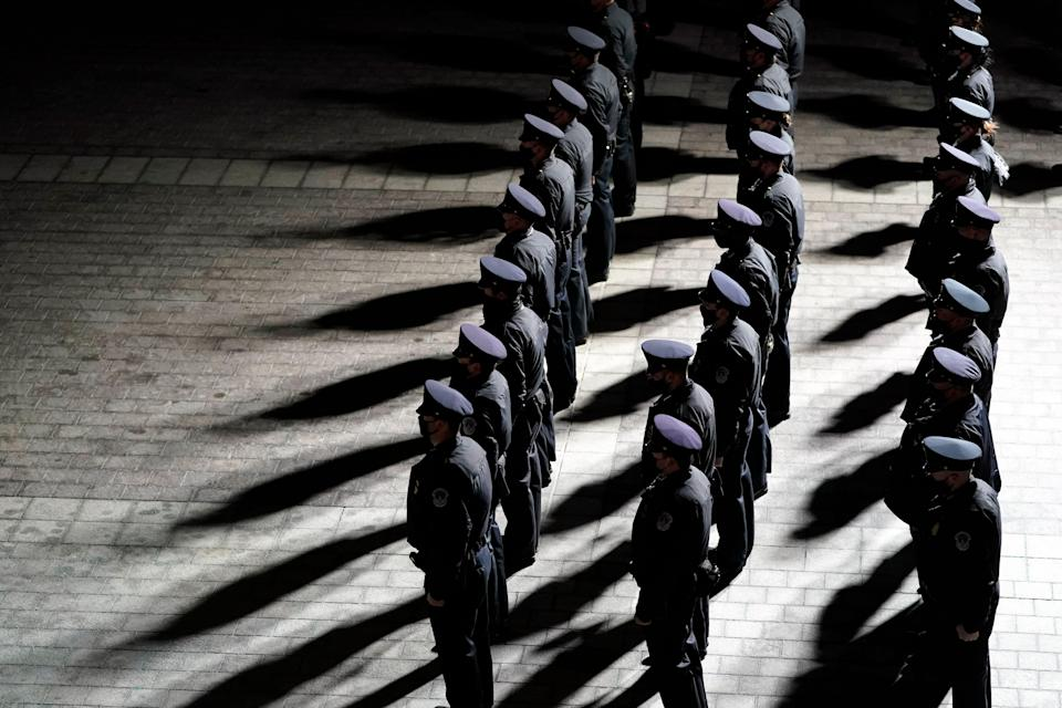 U.S. Capitol Police officers stand at attention as  the cremated remains of officer Brian Sicknick arrive at the U.S Capitol to lie in honor in the Rotunda on Feb. 2 in Washington. Sicknick died the day after the riot Jan. 6.