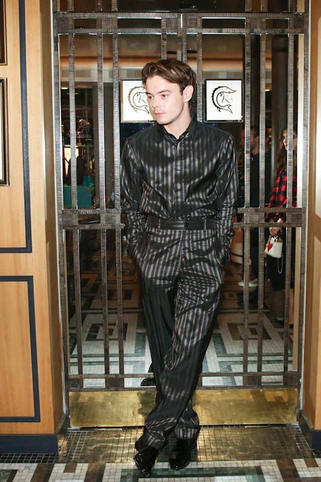 Silk was trending at the Dior dinner. The <em>Stranger Things</em> star posed in a silky black-and-gray suit and classic black shoes.