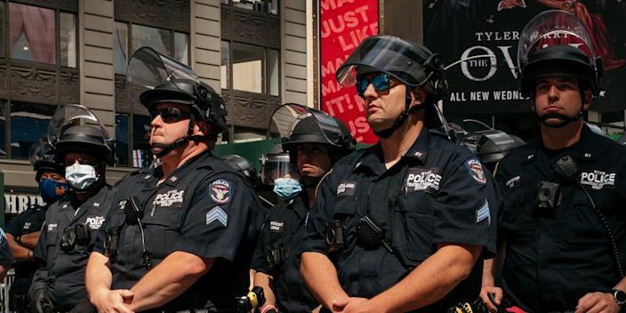 NEW YORK, NY - JUNE 01: NYPD officers stand in formation as nearby demonstrators hold a rally in Times Square denouncing racism in law enforcement and the May 25 killing of George Floyd while in the custody of Minneapolis, on June 1, 2020 in New York City. Days of protest, sometimes violent, have followed in many cities across the country