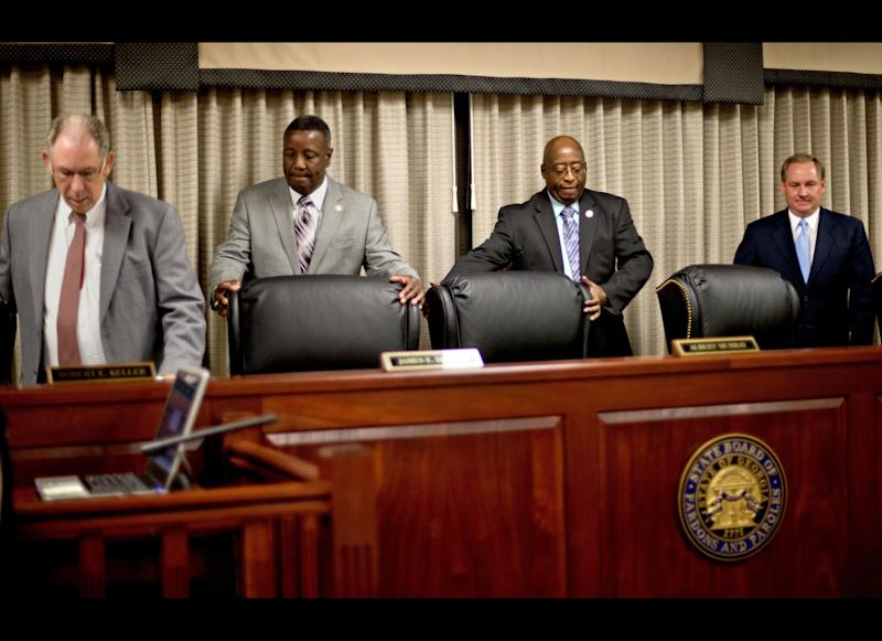 Members of the Georgia Board of Pardons and Paroles, from left, Robert Keller, James Donald, Albert Murray, and James Mills, take their seats for a clemency hearing in the case of death row inmate Warren Lee Hill Friday, July 13, 2012, in Atlanta. Hill's attorneys claim he is mentally disabled and should not be executed next week. Georgia was the first state to ban executing mentally disabled death row inmates, but the case of Hill has highlighted the state's strictest-in-the-nation standard for proving mental disability. (AP Photo/David Goldman)