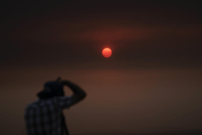Jason Anderson, 42, takes pictures as the sun is visible through thick smoke generated by the Bobcat Fire in San Dimas, Calif., Wednesday, Sept. 9, 2020. Hazy clouds of smoke from dozens of wildfires darkened the sky to an eerie orange glow over much of the West Coast on Wednesday, keeping street lights illuminated during the day and putting residents on edge. (AP Photo/Jae C. Hong)