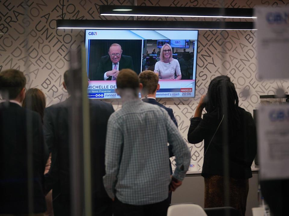 Staff in the green room watching a television screen showing presenters Andrew Neil and Michelle Dewberry broadcast from a studio, during the launch event for new TV channel GB News (Yui Mok/PA)