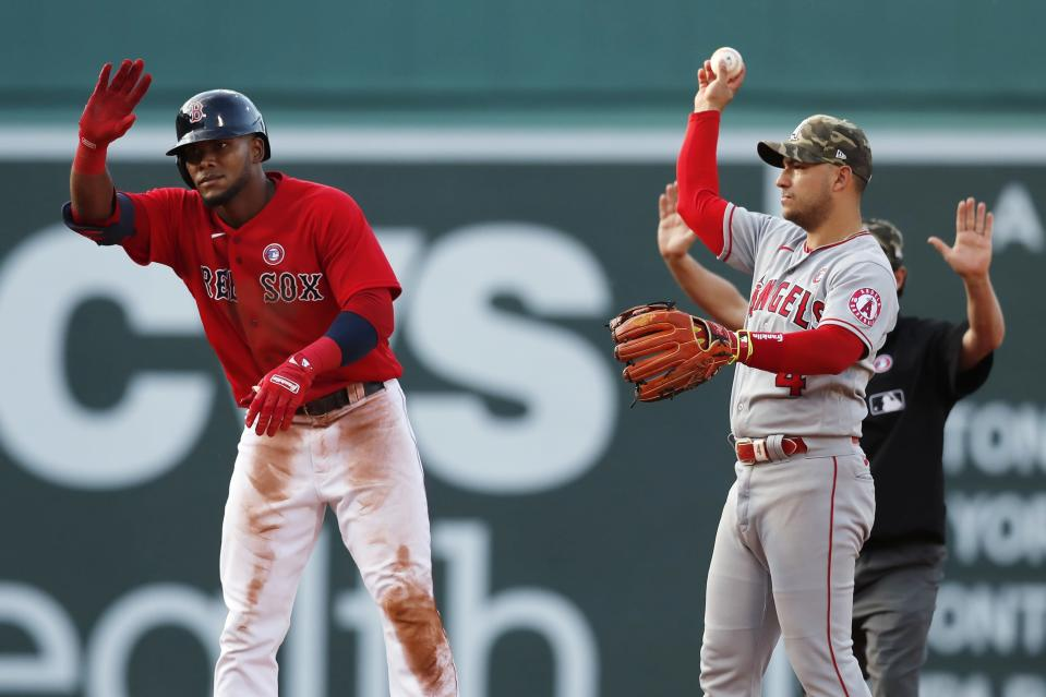 Boston Red Sox's Franchy Cordero, left, reacts after his RBI-double beside Los Angeles Angels' Jose Iglesias (4) during the sixth inning of a baseball game, Saturday, May 15, 2021, in Boston. (AP Photo/Michael Dwyer)