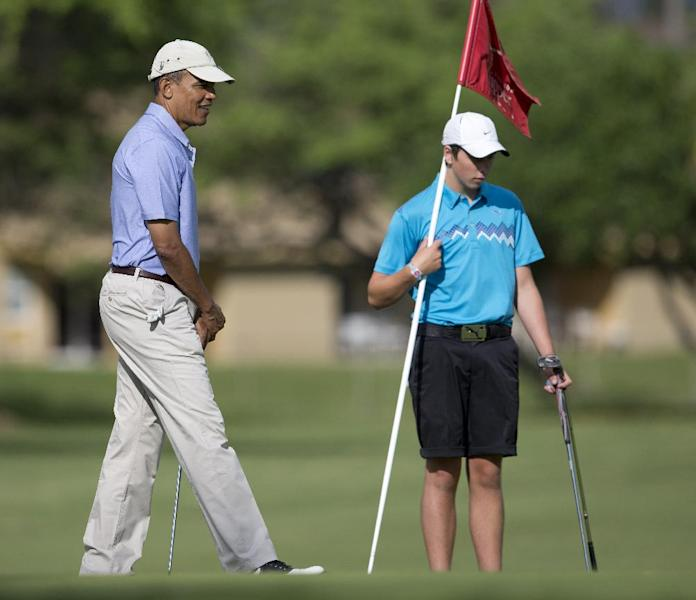 President Barack Obama, left, and Max Key, son of New Zealand Prime Minister John Key, golf on the second green at Kaneohe Klipper Golf Course on Marine Corps Base Hawaii, in Kaneohe Bay, Hawaii, Thursday, Jan. 2, 2014. The first family is in Hawaii for their annual holiday vacation. (AP Photo/Carolyn Kaster)