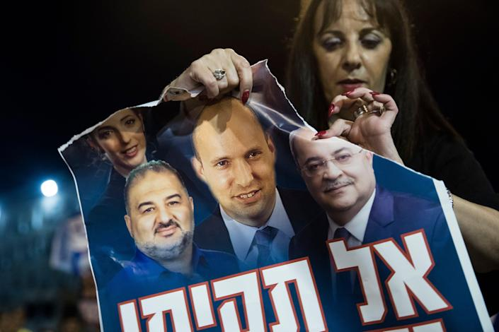An Israeli woman rips a poster showing photos of expected incoming Prime Minister Naftali Bennett and Mansur Abbas, the head of the United Arab List party and lawmaker Ahmed Tibi during a demonstration against the emerging Israeli government on June 10, 2021 in Jerusalem.