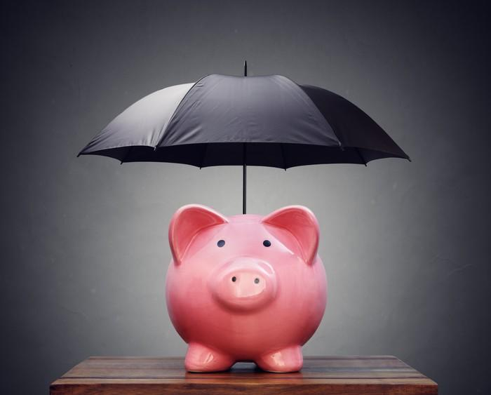 A piggy bank with an umbrella opened above it