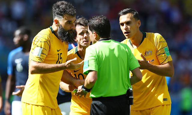 Mile Jedinak, Robbie Kruse and Trent Sainsbury of Australia argue with referee Andres Cunha.
