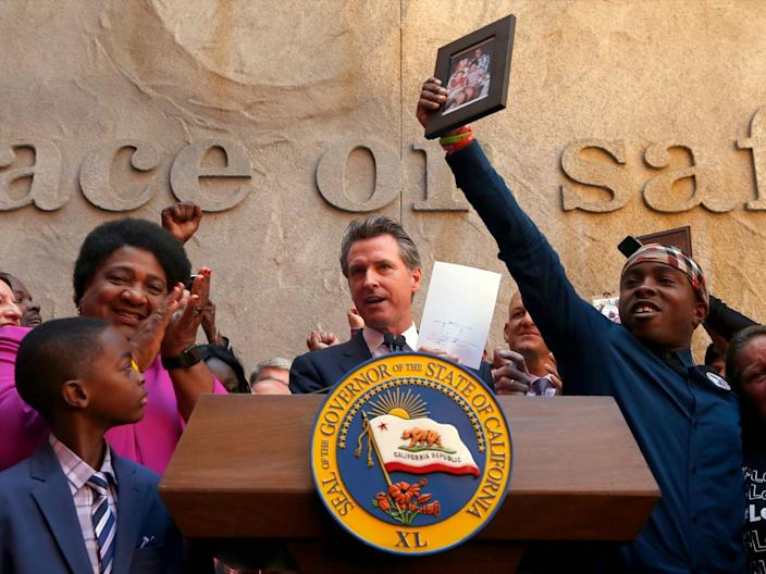 Gov. Gavin Newsom holds up the measure by Assemblywoman Shirley Weber, D-San Diego, left, that he signed that limits the use of lethal force by law enforcement Sacramento, Calif., Monday, Aug. 19, 2019.