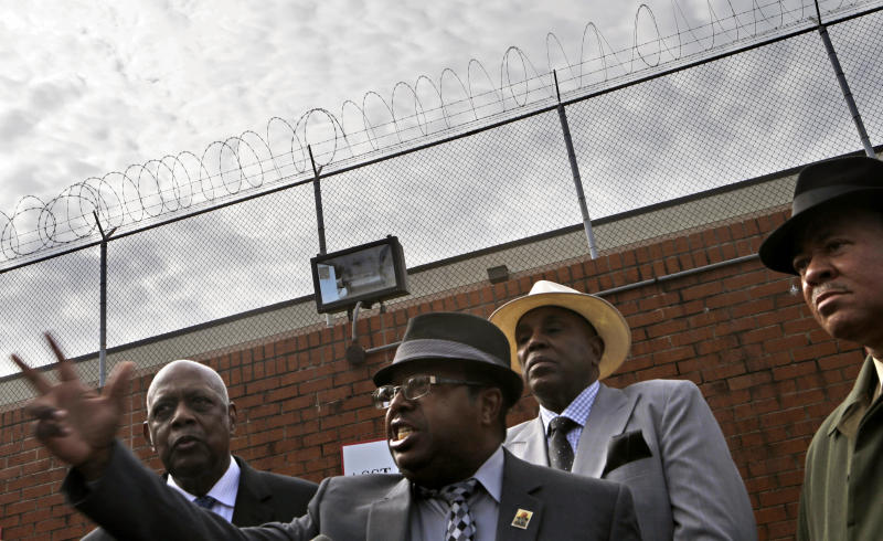 Rev. Timothy McDonald, center, leads a protest against the high bonds set for 35 defendants in Atlanta's school cheating scandal outside the Fulton County Jail, Tuesday, April 2, 2013, in Atlanta. The 35 defendants are named in a 65-count indictment that alleges a broad conspiracy involving cheating on standardized tests in Atlanta Public Schools. All 35 defendants must turn themselves in Tuesday. (AP Photo/David Goldman)