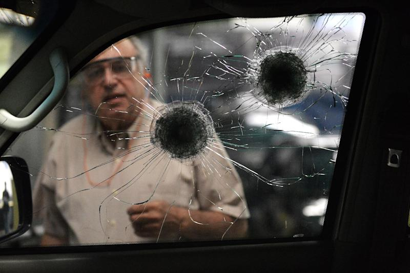 A worker checks the re-inforced windows of a car at a garage making armoured cars in Caracas, on October 21, 2014 (AFP Photo/Federico Parra)