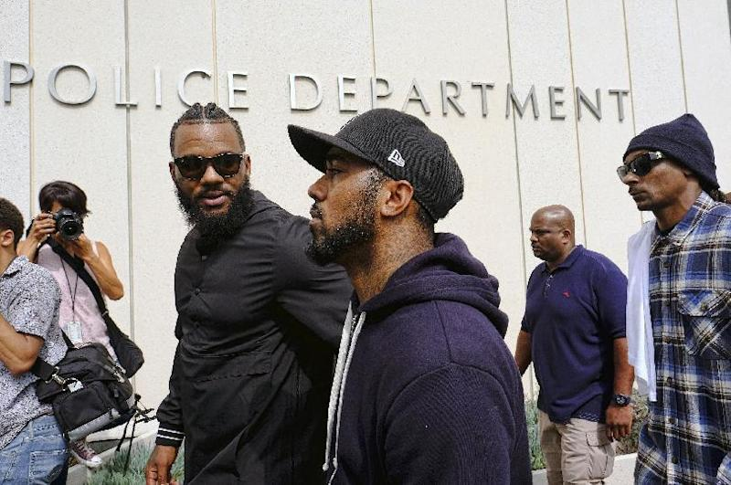 Rappers The Game, left, and Snoop Dogg, right, appear at Los Angeles police headquarters to meet with police Chief Charlie Beck after a peaceful unification march in Los Angeles, Friday, July 8, 2016, after the shooting deaths of multiple police officers in Dallas on Thursday night. (AP Photo/Richard Vogel)