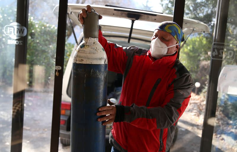 Miralem Sabic carries oxygen bottles from his private van to an improvised coronavirus disease (COVID-19) hospital in Konjic, Bosnia and Herzegovina