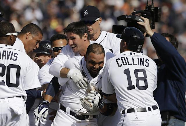 Detroit Tigers' Alex Gonzalez, center, is mobbed after hitting the game winning single to score the winning run from third during the ninth inning of a baseball game against the Kansas City Royals in Detroit, Monday, March 31, 2014. (AP Photo/Carlos Osorio)